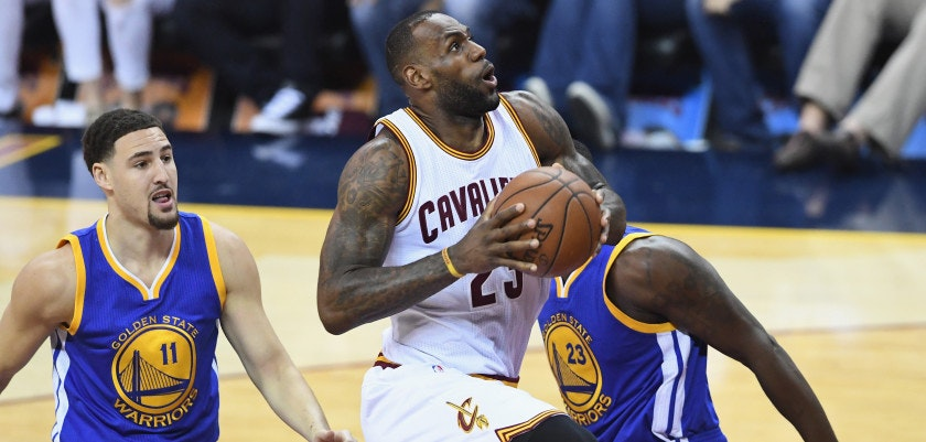 CLEVELAND, OH - JUNE 08:  LeBron James #23 of the Cleveland Cavaliers drives to the basket against Klay Thompson #11 of the Golden State Warriors and Draymond Green #23 during the first half in Game 3 of the 2016 NBA Finals at Quicken Loans Arena on June 8, 2016 in Cleveland, Ohio. NOTE TO USER: User expressly acknowledges and agrees that, by downloading and or using this photograph, User is consenting to the terms and conditions of the Getty Images License Agreement.  (Photo by Jason Miller/Getty Images)