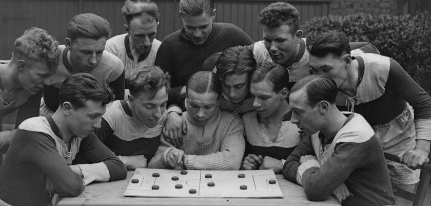 18th March 1935:  Joey Carr (centre), a fly weight boxer studying football tactics on a demonstration board with members of St Marks' Fellowship unemployed football team whom he is coaching.  They are in the final of the London Occupational Shield (the unemployed Cup Final) to be played at Wembley.  (Photo by William Vanderson/Fox Photos/Getty Images)