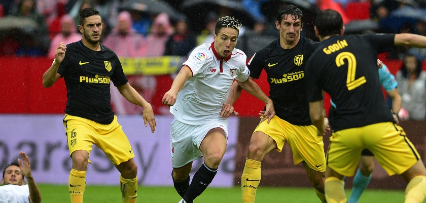 Sevilla's French midfielder Samir Nasri (2nd L) vies with Atletico Madrid's Montenegrin defender Stefan Savic (2nd R) as Atletico Madrid's midfielder Koke (L) looks on during the Spanish league football match between Sevilla FC and Club Atletico de Madrid at the Ramon Sanchez Pizjuan stadium in Sevilla on October 23, 2016. / AFP / CRISTINA QUICLER        (Photo credit should read CRISTINA QUICLER/AFP/Getty Images)