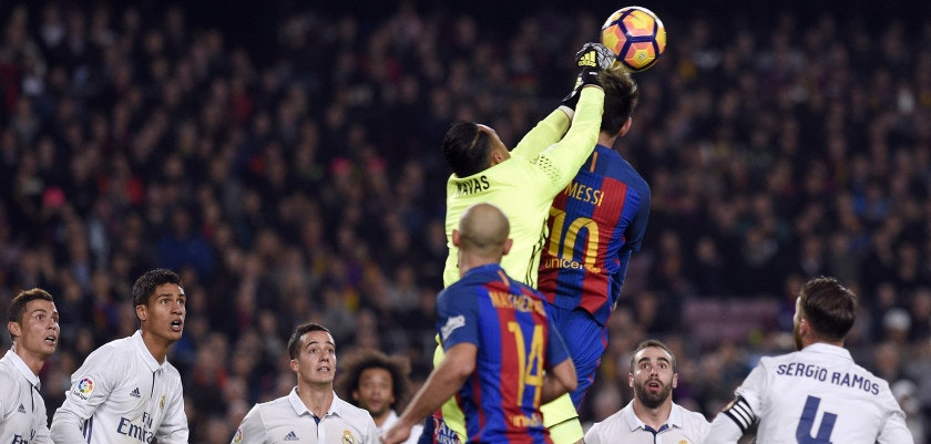Real Madrid's Costa Rican goalkeeper Keylor Navas (top L) jumps for the ball with Barcelona's Argentinian forward Lionel Messi (top R) during the Spanish league football match FC Barcelona vs Real Madrid CF at the Camp Nou stadium in Barcelona on December 3, 2016. / AFP / LLUIS GENE        (Photo credit should read LLUIS GENE/AFP/Getty Images)