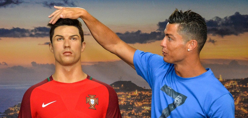 TOPSHOT - Portugese forward Cristiano Ronaldo poses next to a wax statue representing himself during a visit to the new location of the CR7 museum dedicated his professional career at Funchal, on the Portuguese island of Madeira on July 23, 2016.  / AFP / JOANA SOUSA        (Photo credit should read JOANA SOUSA/AFP/Getty Images)