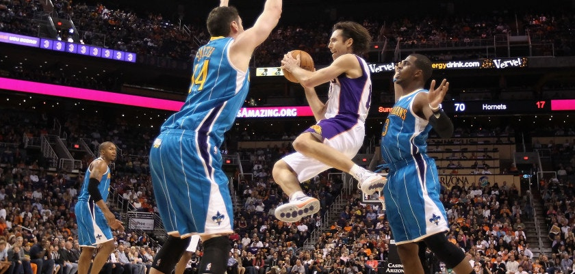 PHOENIX, AZ - JANUARY 30:  Steve Nash #13 of the Phoenix Suns makes a leaping pass guarded by Jason Smith #14 and Chris Paul #3 of the New Orleans Hornets during the NBA game at US Airways Center on January 30, 2011 in Phoenix, Arizona. The Suns defeated the Hornets 104-102. NOTE TO USER: User expressly acknowledges and agrees that, by downloading and or using this photograph, User is consenting to the terms and conditions of the Getty Images License Agreement.  (Photo by Christian Petersen/Getty Images)