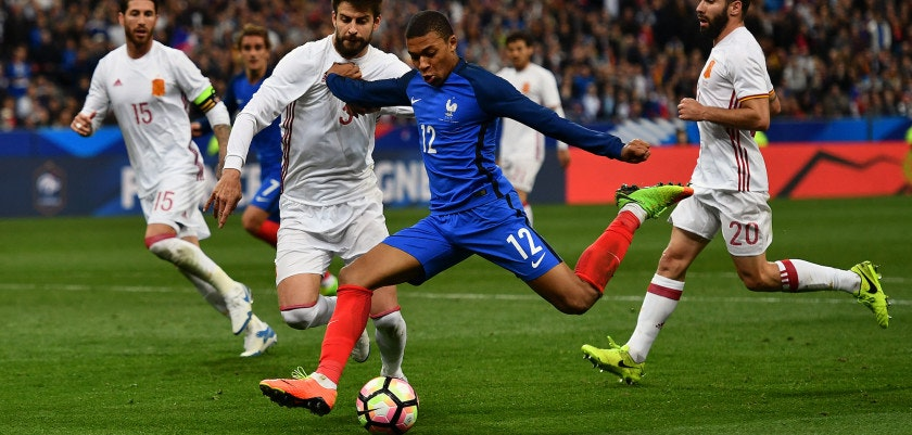 PARIS, FRANCE - MARCH 28:  Kylian Mbappe of France holds off Gerard Pique of Spain to take a shot at goal during the International Friendly match between France and Spain at the Stade de France on March 28, 2017 in Paris, France. (Photo by Dan Mullan/Getty Images)