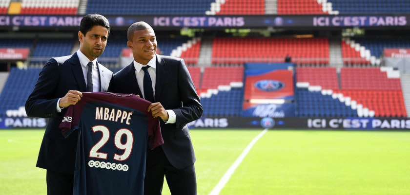 Paris Saint-Germain's new forward Kylian Mbappe (R) together with Paris Saint Germain's Qatari president Nasser Al-Khelaifi holds his jersey during his presentation at the Parc des Princes stadium in Paris on September 6, 2017. The 18-year-old striker moved to PSG in a season-long loan deal with a 180 million euro buy-out clause attached, making him the second most expensive player of all time behind new teammate Neymar. / AFP PHOTO / FRANCK FIFE        (Photo credit should read FRANCK FIFE/AFP/Getty Images)