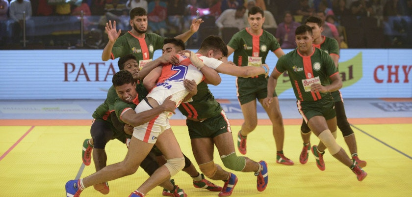 England kabaddi player, Keshav Gupta (C) struggles to free himself from Bangladeshi opponents during a match between England and Bangladesh at the TransStadia in Ahmedabad on October 8, 2016.  The 2016 Kabaddi World Cup tournament runs from October 7 - 22, 2016. / AFP / SAM PANTHAKY        (Photo credit should read SAM PANTHAKY/AFP/Getty Images)