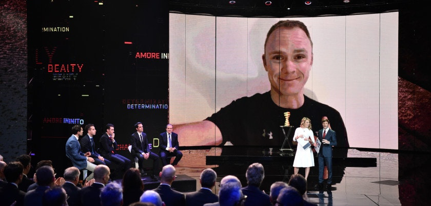"TOPSHOT - Britain's pro cyclist Christopher Froome is seen on a video screen  during the presentation of the 2018 Tour of Italy (101st Giro d'Italia) cycling race, on November 29, 2017 in Milan. ""Ciao (hello) everyone, I'm looking forward to seeing you all on the start line of the 2018 Giro d'Italia,"" Froome said in a short video message played during the 2018 route presentation ceremony in Milan. / AFP PHOTO / MARCO BERTORELLO        (Photo credit should read MARCO BERTORELLO/AFP/Getty Images)"