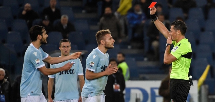 Italian referee Piero Giacomelli (R) presents a red card to Lazio's Italian midfielder Ciro Immobile (C) during the Italian Serie A football match Lazio versus Torino on December 11, 2017 at the Olympic Stadium in Rome. / AFP PHOTO / Andreas SOLARO        (Photo credit should read ANDREAS SOLARO/AFP/Getty Images)