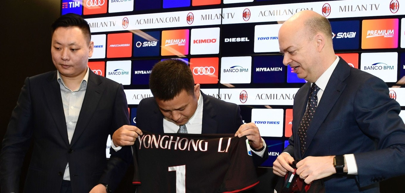 """Head of Rossoneri Sport Investment Lux, Chinese businessman and new owner of the AC Milan football club, Yonghong Li (C) looks at his name on AC Milan's jersey next to Italian businessman Marco Fassone (R) and Rossoneri Sport Investment Lux representative David Han Li (L) during a press conference on April 14, 2017 in Milan.  Serie A giants AC Milan were sold to Rossoneri Sport Investment Lux yesterday in a deal which sees the Chinese-led consortium take a 99.9% stake in the club. The seven-time European champions who are Italy's most succcessful club in international competition, have been owned by former three-time Italy prime minister Silvio Berlusconi since 1986. A joint statement by AC Milan's holding company Fininvest and Rossoneri Sport Investment Lux said on April 13, 2017 : """"Today Fininvest has completed the sale of the entire stake owned in AC Milan - equal to 99.93% - to Rossoneri Sport Investment Lux.""""  / AFP PHOTO / MIGUEL MEDINA        (Photo credit should read MIGUEL MEDINA/AFP/Getty Images)"""