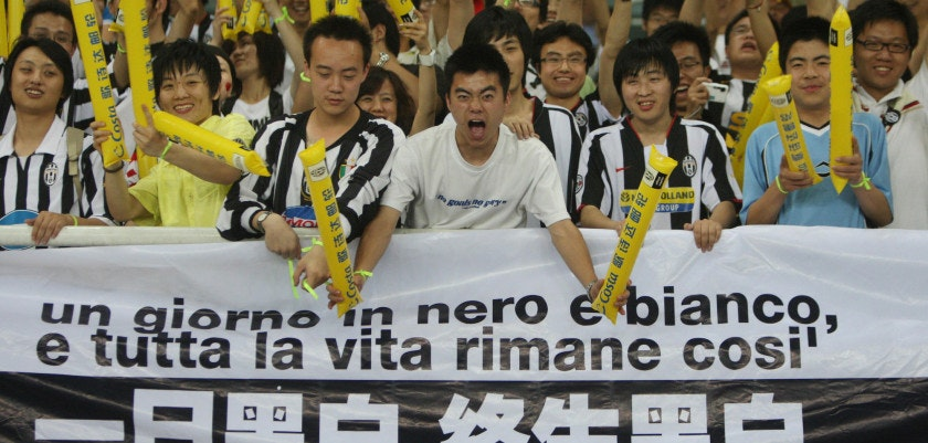 Chinese fans of the Italian team Juventus shout support during their Fiat Cup match against the Chinese Super League club Shanghai Shenhua at the Shanghai Stadium on May 24, 2008. This was the first chance for Italian Serie A fans on the Chinese mainland to get a live look at Juventus, the 27-time Serie A champion team founded in 1897 and  one of the oldest and most renowned clubs in Italy.       AFP PHOTO/Zhu Gang (Photo credit should read ZHU GANG/AFP/Getty Images)
