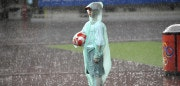 A ball boy holding a ball, stands on the rainy pitch during the 2008 Beijing Olympic Games women's quarter-final football match between Canada and the US at the Shanghai Stadium on August 15, 2008. The US defeated Canada 2-1 with a decisive goal in the extra time, to advance into the semi-final. AFP PHOTO/LIU Jin (Photo credit should read LIU JIN/AFP/Getty Images)