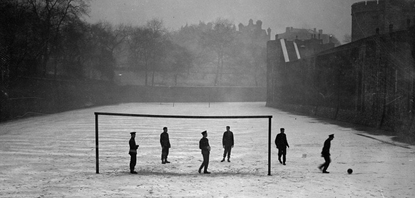 Guards play football in the snow at the Tower of London.    (Photo by Fox Photos/Getty Images)