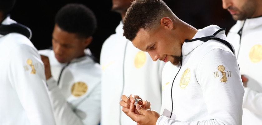 OAKLAND, CA - OCTOBER 17:  Stephen Curry #30 of the Golden State Warriors looks at his 2017 NBA Championship ring prior to their NBA game against the Houston Rockets at ORACLE Arena on October 17, 2017 in Oakland, California. NOTE TO USER: User expressly acknowledges and agrees that, by downloading and or using this photograph, User is consenting to the terms and conditions of the Getty Images License Agreement.  (Photo by Ezra Shaw/Getty Images)