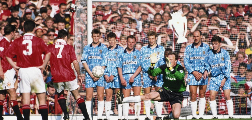 MANCHESTER, UNITED KINGDOM - MAY 08:  Coventry City goalkeeper Steve Ogrizovic and the City defensive wall attempt to stop a free kick from Eric Cantona as a fan from behind the goal waves a foil Premier League trophy during the final game of the 1993/94 season, as champions Manchester United draw 0-0 with Coventry City at Old Trafford on May 8, 1994 in Manchester, England. (Photo by David Cannon/Allsport/Getty Images)
