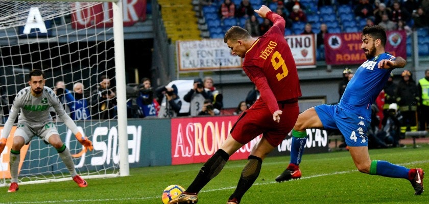 AS Roma's Bosnian forward Edin Dzeko (C) kicks the ball during the Italian Serie A football match AS Roma versus Sassuolo on December 30, 2017 at the Olympic stadium in Rome.  / AFP PHOTO / Vincenzo PINTO        (Photo credit should read VINCENZO PINTO/AFP/Getty Images)