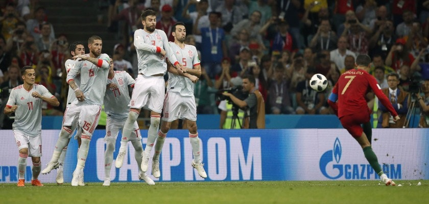 Portugal's forward Cristiano Ronaldo (R) scores his third goal from a freekick during the Russia 2018 World Cup Group B football match between Portugal and Spain at the Fisht Stadium in Sochi on June 15, 2018. (Photo by Odd ANDERSEN / AFP) / RESTRICTED TO EDITORIAL USE - NO MOBILE PUSH ALERTS/DOWNLOADS        (Photo credit should read ODD ANDERSEN/AFP/Getty Images)