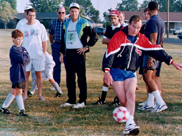 U.S. President George Bush (R) kicks a soccer ball