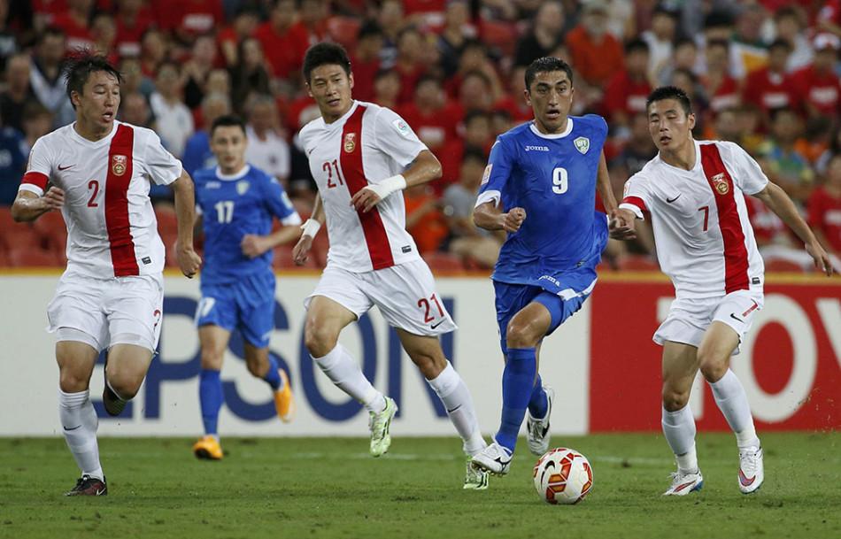 Uzbekistan's Odil Akhmedov runs past China's Ren Hang, Yu Hai and Wu Lei during their Asian Cup Group B soccer match at the Brisbane Stadium in Brisbane